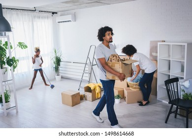 Young African-american Family Unpacking and Cleaning. Move into New Home.