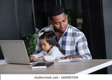 Young African-american father a designer at a remote work works at a computer sits at a table with his charming little two-year-old daughter. Concept of combining work and family