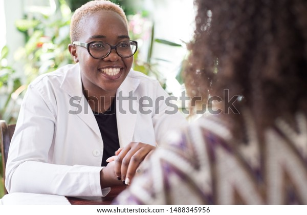A young African-American female doctor with glasses shakes hands with a patient as a sign of trust of a doctor. People of mixed race. In the doctor's office