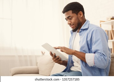 Young african-american guy using digital tablet, connecting wifi at home, empty space