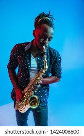 Young african-american jazz musician playing the saxophone on blue studio background in trendy neon light. Concept of music, hobby. Joyful attractive guy improvising. Retro colorful portrait of artist