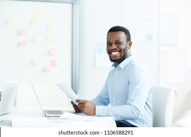 Young african-american male sitting at desk with laptop and papers tidy office in smiling and looking at camera