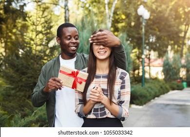 Young african-american man with giftbox closing his girlfriend eyes to make surprise for her, walking in park