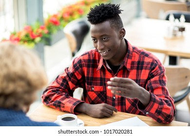 Young African-american man having talk to his friend or colleague by cup of coffee in cafe