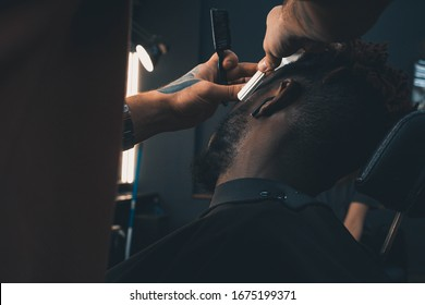 Young African-american man visiting barbershop. Brings a beard in order with the help of a hairdresser.  Self-care, masculine beauty.  Black African Hair Trimmer.