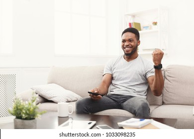 Young african-american man watching tv on the couch, happy of favourite football team, pointing with remote controller on tv-set, copy space
