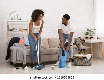 Young african-american man and woman cleaning messy room after party, smiling to each other