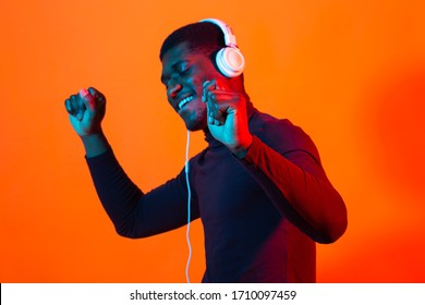 Young african-american man's listening to music in headphones in neon light. Male portrait. Concept of human emotions, facial expression, holidays or weekend, hobby,