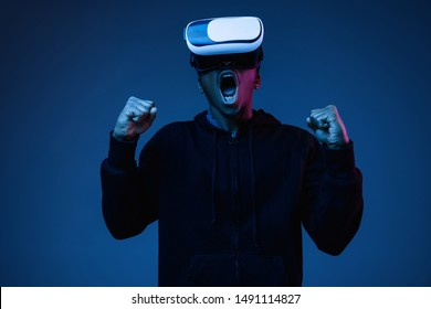 Young african-american man's screaming in VR-glasses in neon on gradient background. Male portrait. Concept of human emotions, facial expression, modern gadgets and technologies. Look like winner.