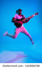 Young african-american musician playing the guitar in jump like a rockstar on blue studio background in neon light. Concept of music, hobby. Joyful attractive guy improvising. Retro colorful portrait.