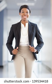 Young African-american professional woman walking down a hallway towards camera, smiling, wearing blazer, pearls