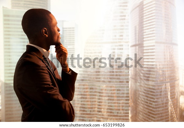 Young african-american thoughtful businessman wearing suit holding hand on chin, looking out of big office window at sunset city building lost in thoughts, planning future project. Side view copyspace