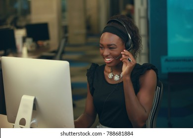 Young African-American woman cheerfully smiling and touching headset microphone while working on computer in office.