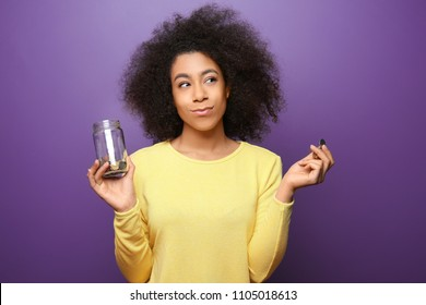 Young African-American woman holding glass jar with coins on color background. Savings concept