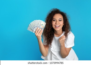 Young African-American woman with money on color background. Space for text