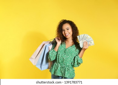 Young African-American woman with money and shopping bags on color background