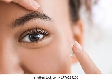 Young African-American woman putting in contact lenses, closeup