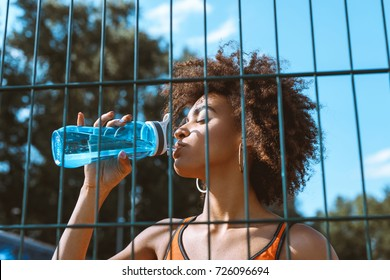 young african-american woman in sportive attire drinking from a water bottle behind wired fencing