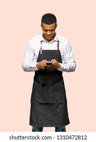 Young afro american barber man sending a message with the mobile on isolated background