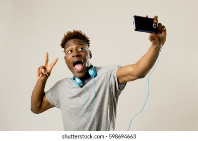 young afro american black man smiling happy taking selfie self portrait picture with mobile phone looking excited having fun posing cool isolated in grey  background in communication technology