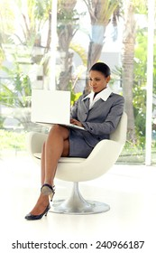 Young Afro American businesswoman using laptop in lobby