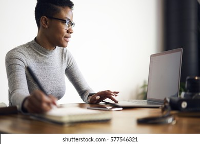 Young afro american female executive  filling in application on official site of media marketing corporation ordering services and collaboration via laptop computer and wireless internet indoor