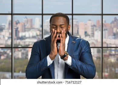 Young afro american in full disbelief. Black man with closed eyes holds hand near opened mouth. Upset black businessman.