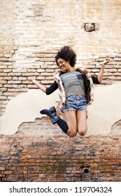 Young afro american girl jumping in urban background