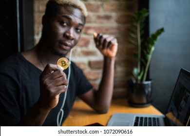 Young afro american man with bitcoin in hand in front of laptop in cafeteria