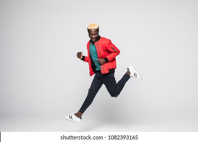 Young afro american man jumping over isolated white background.