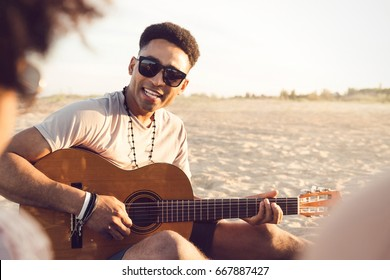Young afro american man playing guitar for friends while sitting on the beach