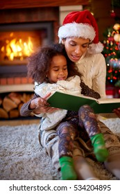 Young afro American mom with daughter reading Christmas fairytales