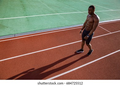 Young afro american runner resting after competition at the stadium