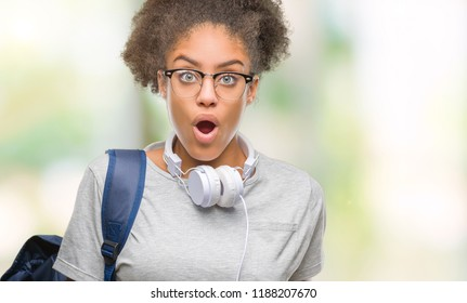 Young afro american student woman wearing headphones and backpack over isolated background afraid and shocked with surprise expression, fear and excited face.