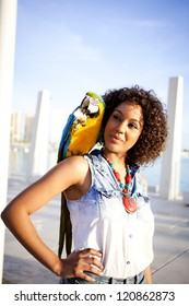 Young afro american woman with a blue macaw on her shoulder in the city
