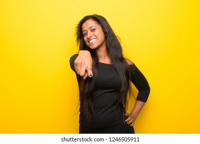 Young afro american woman on vibrant yellow background points finger at you with a confident expression