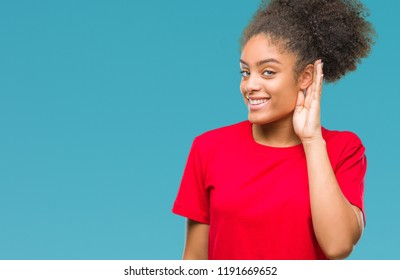 Young afro american woman over isolated background smiling with hand over ear listening an hearing to rumor or gossip. Deafness concept.