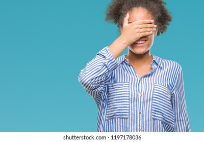 Young afro american woman over isolated background smiling and laughing with hand on face covering eyes for surprise. Blind concept.
