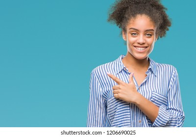 Young afro american woman over isolated background cheerful with a smile of face pointing with hand and finger up to the side with happy and natural expression on face looking at the camera.
