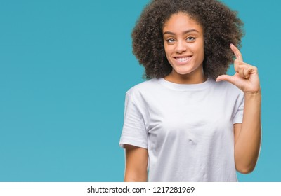 Young afro american woman over isolated background smiling and confident gesturing with hand doing size sign with fingers while looking and the camera. Measure concept.