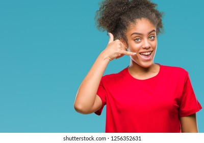 Young afro american woman over isolated background smiling doing phone gesture with hand and fingers like talking on the telephone. Communicating concepts.