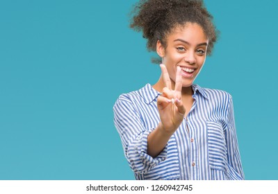 Young afro american woman over isolated background smiling looking to the camera showing fingers doing victory sign. Number two.