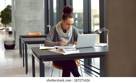 Young afro american woman sitting at table with books and laptop for finding information. Young student taking notes from laptop and books for her study in library.