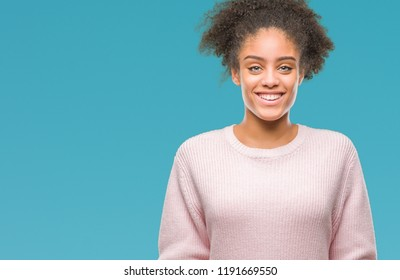 Young afro american woman wearing winter sweater over isolated background with a happy and cool smile on face. Lucky person.