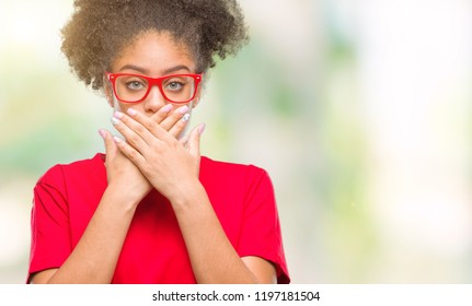 Young afro american woman wearing glasses over isolated background shocked covering mouth with hands for mistake. Secret concept.