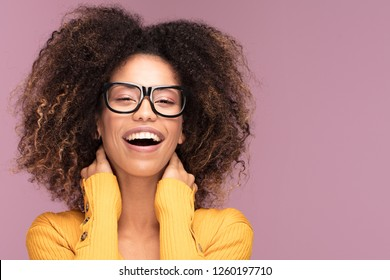 Young afro american woman wearing glasses over pink background smiling .