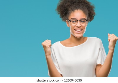 Young afro american woman wearing glasses over isolated background celebrating surprised and amazed for success with arms raised and open eyes. Winner concept.