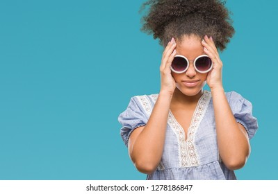 Young afro american woman wearing glasses over isolated background suffering from headache desperate and stressed because pain and migraine. Hands on head.