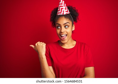 Young afro american woman wearing birthday hat over isolated red background smiling with happy face looking and pointing to the side with thumb up.