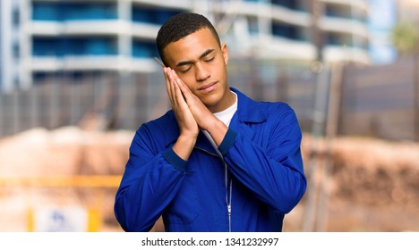 Young afro american worker man making sleep gesture in dorable expression in a construction site